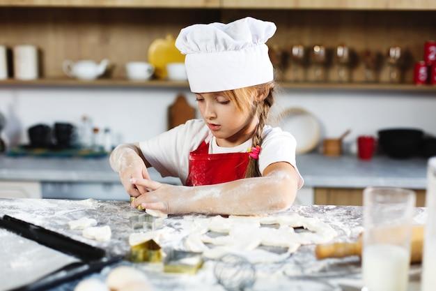 Menina encantadora se diverte fazendo biscoitos de massa em uma cozinha aconchegante