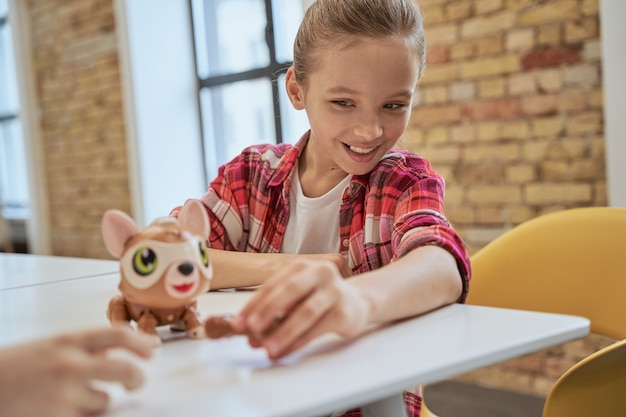 Menina encantadora sentada à mesa examinando o brinquedo técnico e sorrindo, passando o tempo