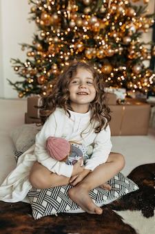 Menina encantadora sentada no travesseiro com o brinquedo na árvore de natal, clima de ano novo, festa de natal
