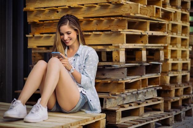 Menina encantadora, sentado em um palete usando telefone inteligente