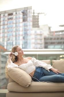 Menina encantadora, sentado em um sofá, em um terraço, ouvindo música com fones de ouvido