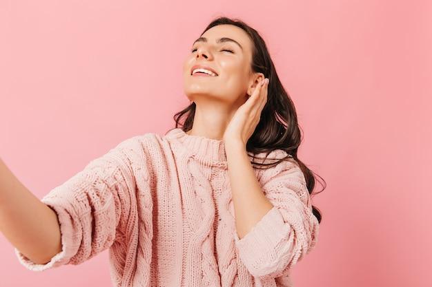 Menina encantadora sorri com os olhos fechados. senhora com um lindo suéter tira selfie no estúdio rosa.