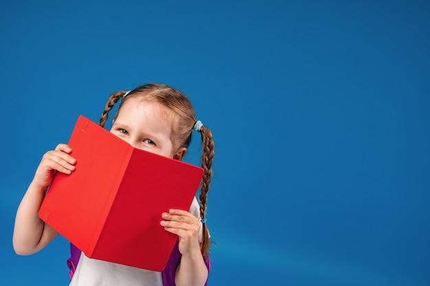 Menina encantadora sorri e se esconde atrás de um livro