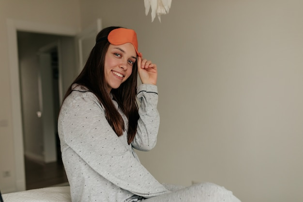 Menina encantadora sorridente fraca em casa em seu quarto branco moderno de pijama e máscara de dormir, olhos abertos e olhando para a janela.