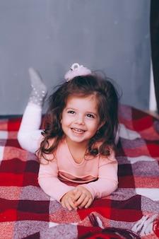 Menina encaracolada bonita encontra-se em uma manta vermelha
