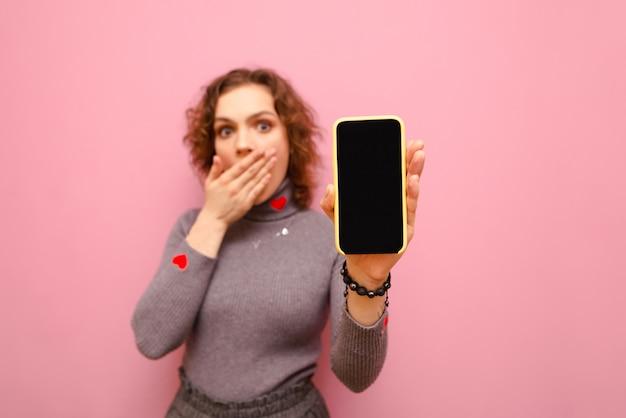 Menina encaracolada chocada cobriu a boca com a mão, segurando um smartphone com uma tela preta na mão