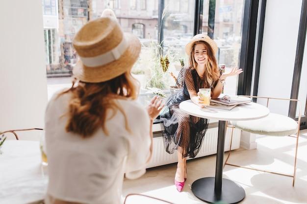 Menina encaracolada com camisa branca e chapéu contando uma história engraçada para um amigo de cabelos compridos bebendo um coquetel