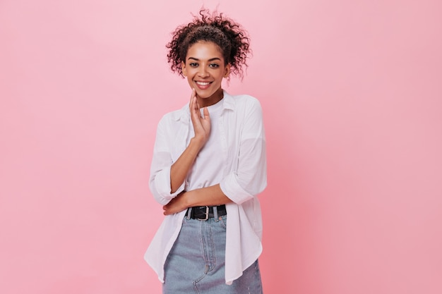 Menina encaracolada de camisa branca sorrindo na parede rosa