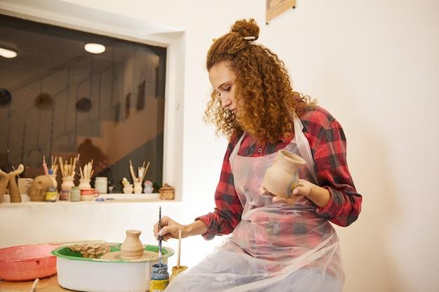 Menina encaracolada está moldando um vaso