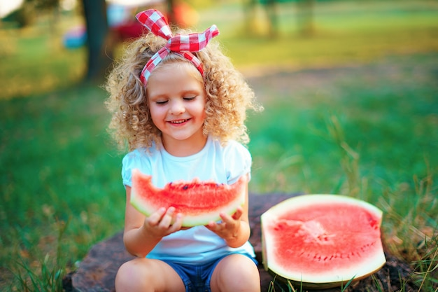 Menina encaracolada feliz sentado no tronco e comendo melancia ao ar livre no parque primavera