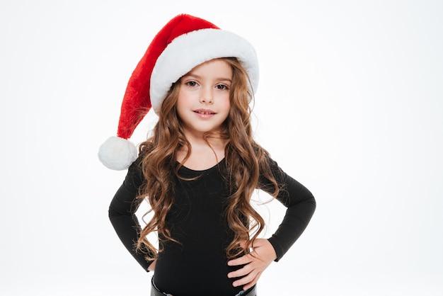 Menina encaracolada no chapéu de papai noel em pé e posando