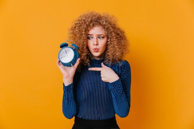 Menina encaracolada no suéter listrado azul olha para o despertador com suspeita e aponta o dedo para ele.