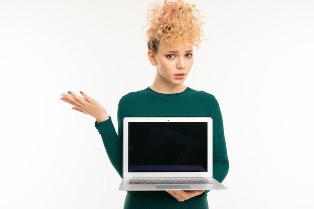 Menina encaracolada segurando um laptop com maquete nas mãos na parede branca