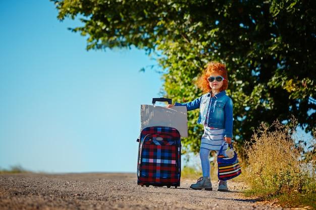 Menina encaracolado consideravelmente pequena que senta-se em uma mala de viagem na estrada e que espera um ônibus ou um carro no dia ensolarado.