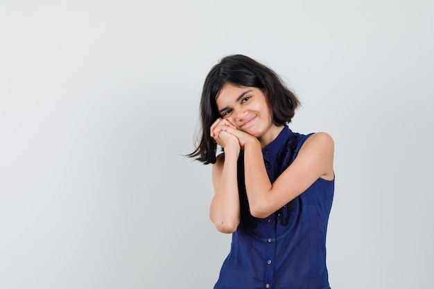 Menina encostando a bochecha nas mãos entrelaçadas na blusa azul e está linda.