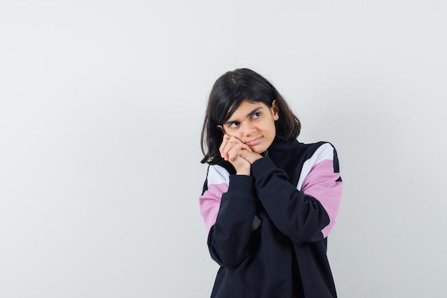 Menina encostando a bochecha nas mãos entrelaçadas na camisa e parecendo um sonho, vista frontal.