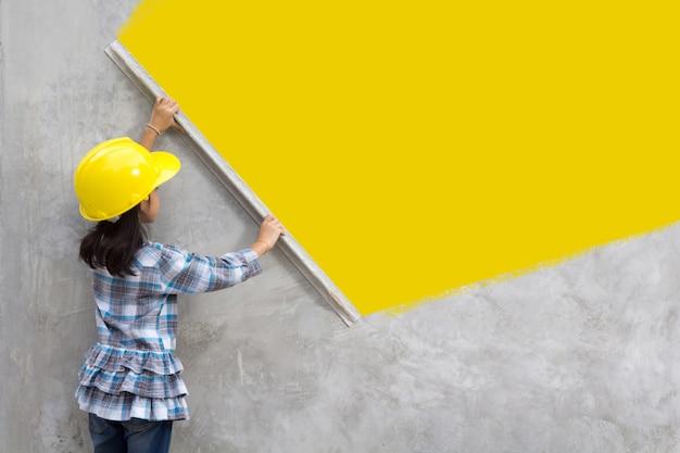 Menina engenharia com a mão segurando ferramentas de reboco na parede