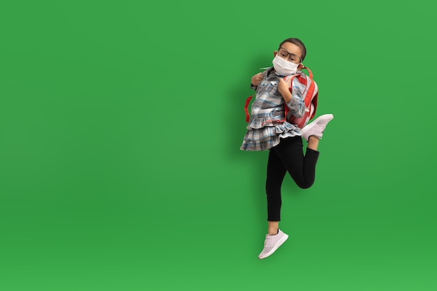 Menina engraçada asiática usando máscaras médicas sobre fundo verde