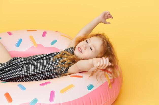 Menina engraçada bonita num vestido arrepiante, deitada no círculo inflável rosa levantando as mãos e sorrindo alegremente