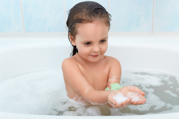 Menina engraçada, brincando com água e espuma na banheira grande