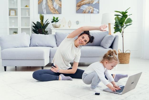 Menina engraçada, brincando com o laptop, enquanto sua mãe saudável desportiva, tendo treinamento de ioga on-line em casa.