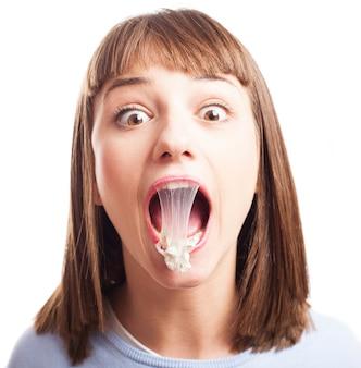Menina engraçada com a goma de mascar na boca