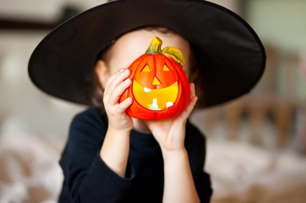 Menina engraçada com fantasia de bruxa para o halloween com a abóbora jack nas mãos