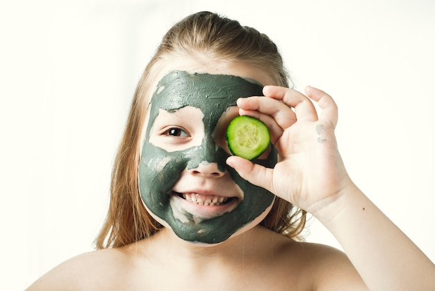 Menina engraçada com máscara de argila cosmética na toalha de banho