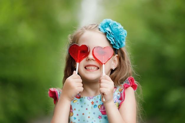 Menina engraçada com pirulitos em forma de coração, mostra os dentes brancos.