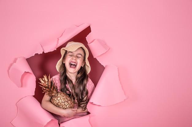 Menina engraçada com um chapéu de praia e com a cor do abacaxi dourado, sobre um fundo colorido rosa, espiando pelo buraco no fundo, tiro no estúdio, espaço para texto