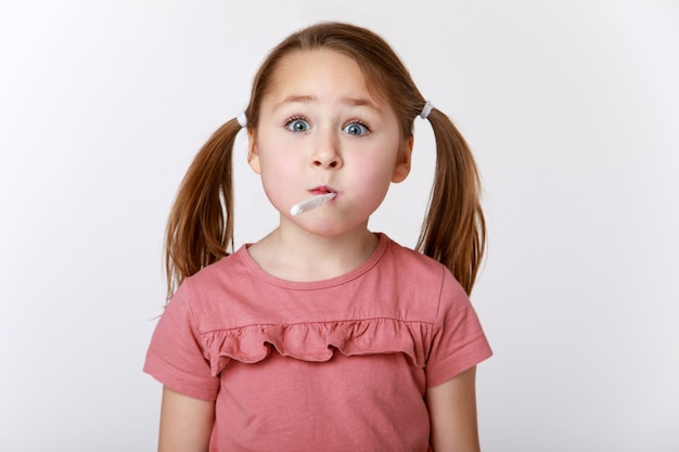 Menina engraçada com uma escova de dentes na boca