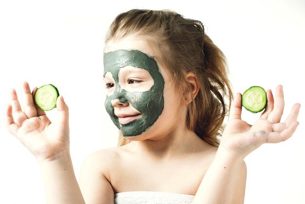 Menina engraçada com uma máscara cosmética feita de barro