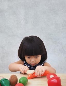 Menina engraçada criança asiática brincando com brinquedo de cozinha de madeira, pequeno chef preparando comida no balcão da cozinha.