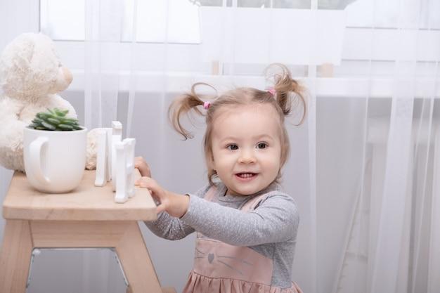 Menina engraçada da criança brincando com brinquedos em casa na sala branca.