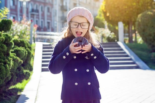 Menina engraçada de óculos com prazer comendo rosquinha de chocolate