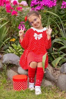 Menina engraçada de óculos e um vestido vermelho com bolinhas