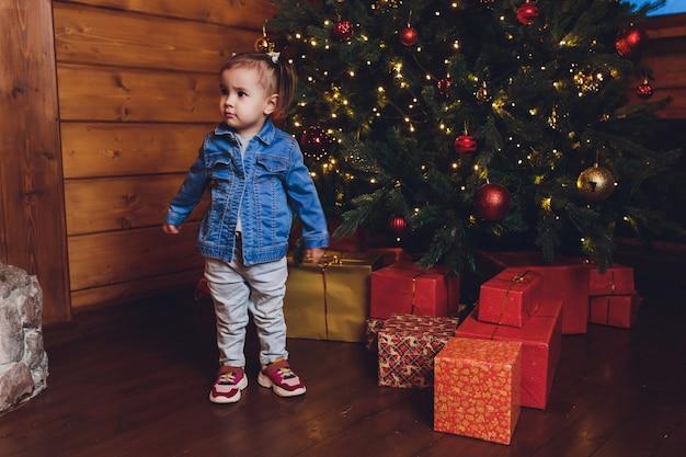 Menina engraçada, decorando a árvore de natal