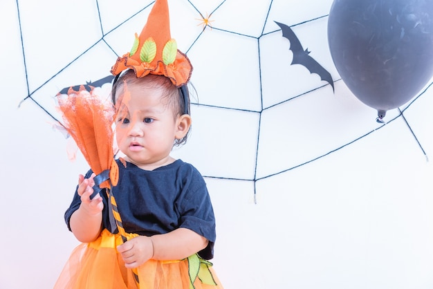 Menina engraçada e feliz com fantasia de halloween com jack de abóbora com teia de aranha