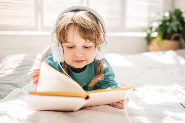 Menina engraçada em um vestido azul lendo um livro em uma cama branca em um quarto ensolarado
