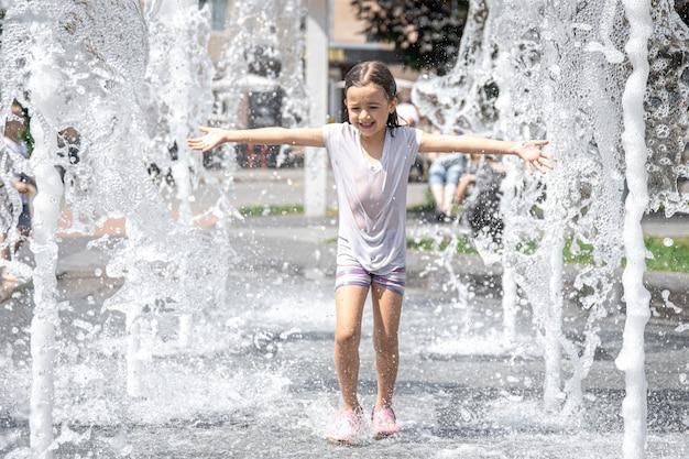 Menina engraçada em uma fonte, entre os salpicos de água em um dia quente de verão.