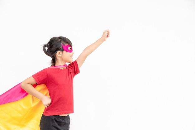 Menina engraçada jogando super-herói de poder sobre fundo branco. conceito de super-herói.
