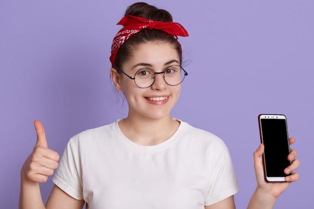 Menina engraçada jovem morena em uma camiseta branca casual posando isolada no espaço lilás