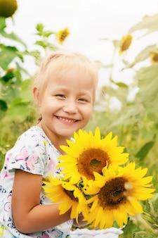 Menina engraçada no campo com flores de girassol, horário de verão