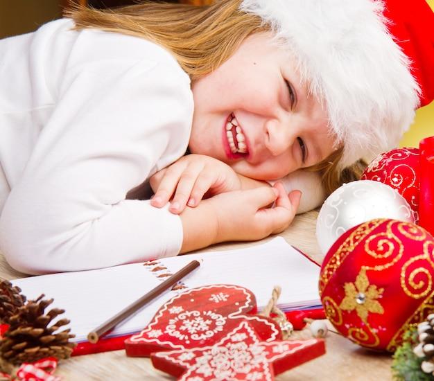 Menina engraçada no chapéu de papai noel escreve carta para o papai noel perto da decoração de natal