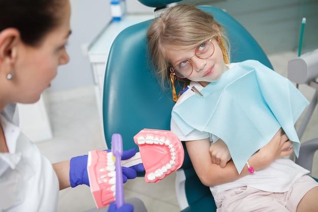 Menina engraçada parecendo irritada, revirando os olhos enquanto o dentista a ensina sobre higiene dos dentes