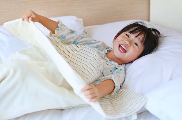 Menina engraçada que encontra-se na cama com cobertor.