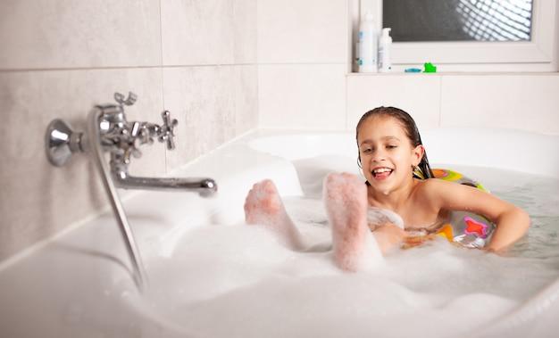 Menina engraçada se banha em uma banheira com uma bóia salva-vidas inflável e com espuma na água. conceito de higiene e entretenimento para crianças. espaço de publicidade