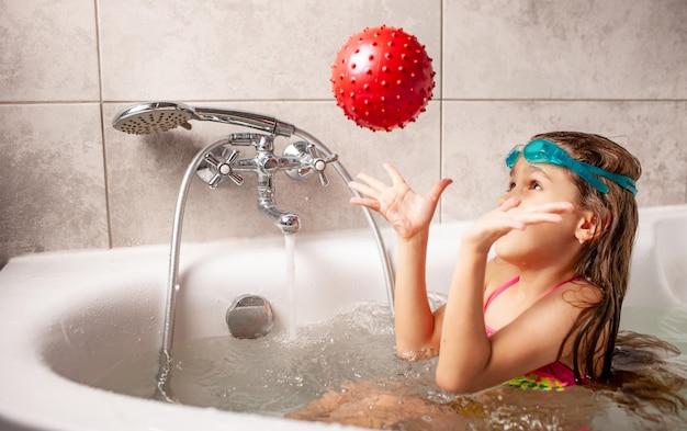 Menina engraçada sorridente em um maiô gosta de jogar bola enquanto toma banho