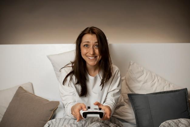 Menina engraçada sorridente joga videogame no console com emoção antes de dormir
