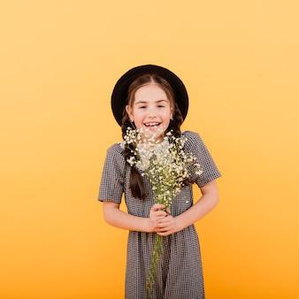 Menina engraçada sorrindo com um buquê de flores em um fundo colorido